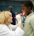 Kevin Gaines, 10, third grader at Rawlings Elementary, has his teeth examined by Sharon Cooper, DMD.